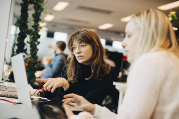 Young businesswoman pointing at laptop to female colleague sitting in office