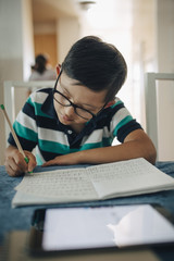Close-up of disabled boy writing on book with digital tablet in foreground at table