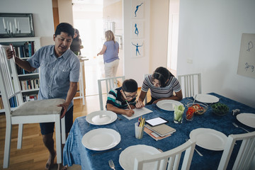 Teenage girl assisting brother in homework while father arranging chairs at dining table