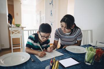 Teenage girl assisting brother in homework at dining table