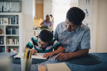 Father assisting son in homework while sitting at table