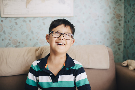 Thoughtful disabled boy laughing while sitting on sofa at home