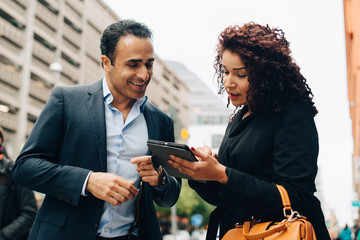 Low angle view of businesswoman discussing over digital tablet to businessman while standing on sidewalk in city