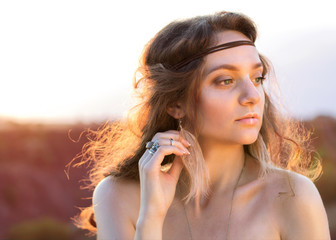 Charming portrait of a hippie girl with earrings feathers and rings on her fingers in vintage style on the sunset
