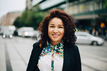 Portrait of smiling mid adult businesswoman standing on street in city