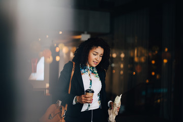 Mid adult businesswoman holding food and drink while walking in cafe