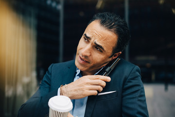 Mature businessman talking from smart phone while holding disposable coffee cup against building in city