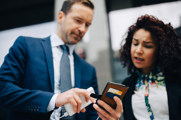 Low angle view of businessman and businesswoman sharing smart phone in city