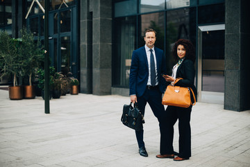 Full length portrait of confident businessman and businesswoman standing against building in city