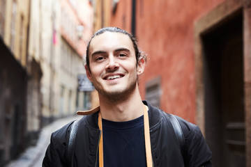 Close-up portrait of smiling young man against buildings in alley