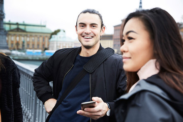 Smiling man standing with female friends on bridge in city