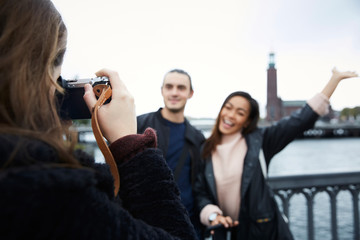 Woman photographing happy friends standing on bridge in city