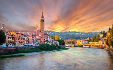Beautiful old houses on Adige river and tower of Santa Anastasia church in Verona at sunser, Veneto region, Italy.