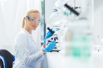 Delighted female biologist sitting in front of the microscope