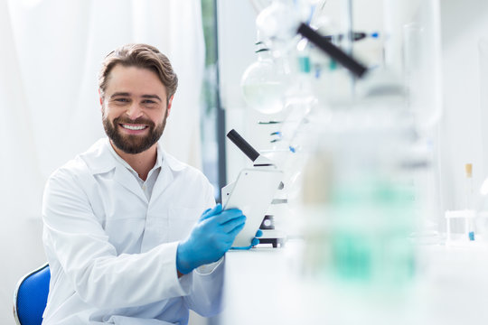 Cheerful male scientist smiling to you