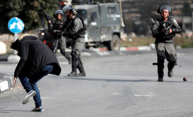Israeli border policemen stand away while shooting a Palestinian man near the Jewish settlement of Beit El, near the West Bank city of Ramallah.