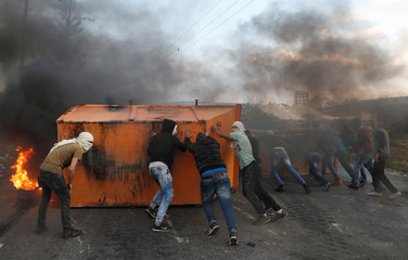 Palestinian protesters set up a barricade during a protest against U.S. President Donald Trump's decision to recognize Jerusalem as the capital of Israel, near the Jewish settlement of Beit El, near the West Bank city of Ramallah