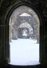 snow falling through a ruined okd church door in heptonstall in west yorkshire
