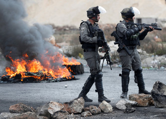 Israeli border policemen stand on a road during a protest against U.S. President Donald Trump's decision to recognize Jerusalem as the capital of Israel, near the Jewish settlement of Beit El, near the West Bank city of Ramallah