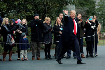 U.S. President Donald Trump waves as he walks on South Lawn of the White House in Washington