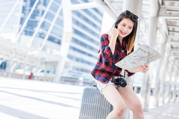 Asia woman travel and using a smart phone and map in the street in a sunny summer day with blur city background