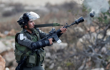 An Israeli border policeman fires a tear-gas canister during a protest against U.S. President Donald Trump's decision to recognize Jerusalem as the capital of Israel, near the Jewish settlement of Beit El, near the West Bank city of Ramallah
