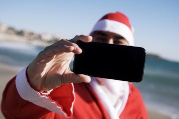 santa claus taking a selfie on the beach