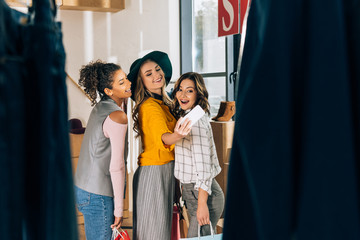 group of happy young women taking selfie in clothing store