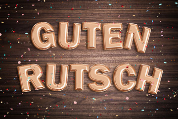 """Luftballons formen den Spruch """"Guten Rutsch"""" auf Holzuntergrund mit Konfetti"""