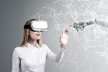 Woman in VR glasses, robot hand