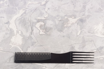 Single black color plastic comb on gray cracked old concrete