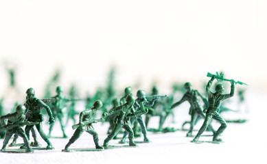Many green army plastic toy soldiers organized on top of a white surface and background, isolated, with out of focus plastic soldiers in the background