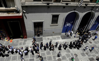 Investors line up at the main entrance of B3 building before they attend an auction to award licenses for investors to build and operate almost 5,000 kilometers of power transmission lines, in Sao Paulo