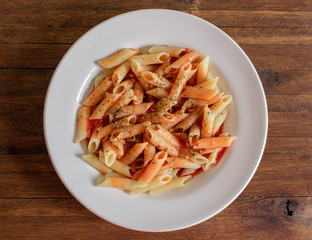 Cooked Penne Pasta Dish, with vibrant red tomato sauce on top, and sprinkled oregano, on a white porcelain plate, dark wood background tabletop