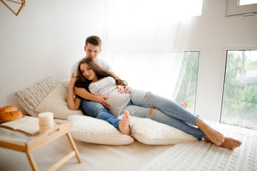 Man with beautiful pregnant woman lying on the bed in a white room