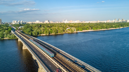 Aerial top view of Metro railway bridge with train and Dnieper river from above, skyline of city of Kiev, Ukraine