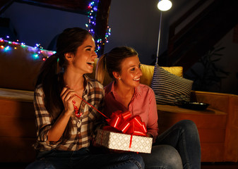 Young woman opens a gift which she got from her friend.Celebration concept.
