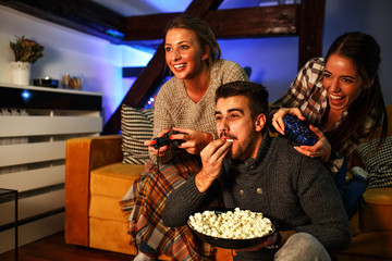 Two female best friends sitting at home on pleasant evening and playing games on console.They challenge each other to win while man cheering and eat popcorn.