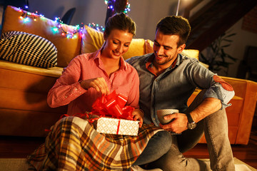 Young woman opens a gift which she got from her husband.Valentine's day concept.