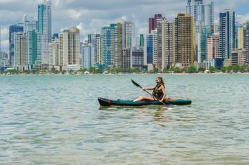 Jovem mulher loira passeando de caiaque em praia do brasil com prédios no fundo, praia e metrópole