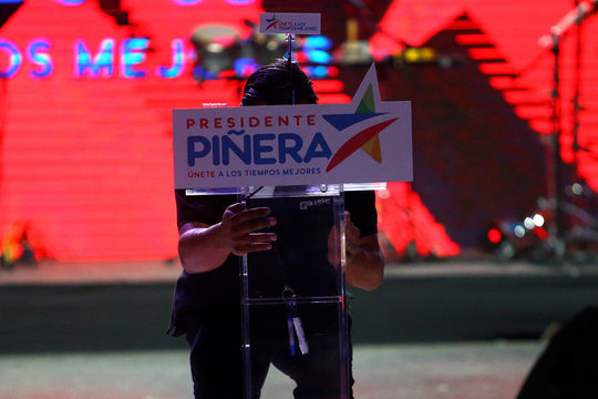 A man prepares the podium where Chilean presidential candidate Sebastian Pinera will give a speech at his closing campaign rally in Santiago,