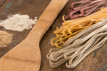 Three coloured dry pasta over wooden top with wooden spoon