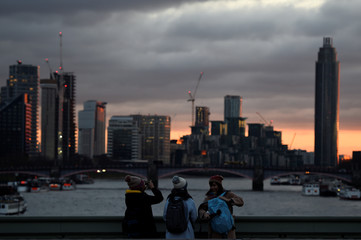 Tourists take pictures on Westminster Bridge during sunset in London
