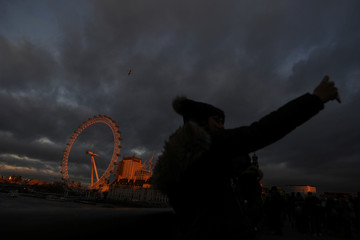 People take a selfie on Westminster Bridge as the London Eye is illuminated by a sunset in London