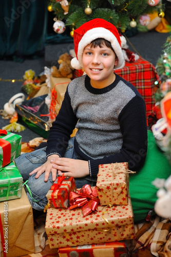 The Christmas Clause.Young Boy With Happy Face And Santa Clause Hat Sitting Near