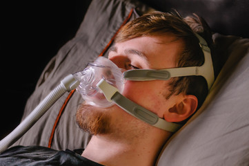 A young man in bed at night using a CPAP machine with face mask