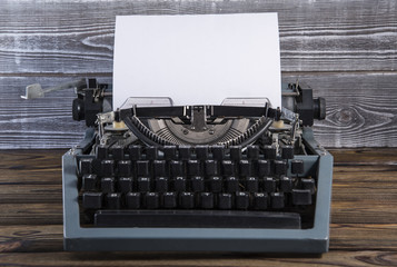 Vintage old typewriter with blank paper on a wooden table
