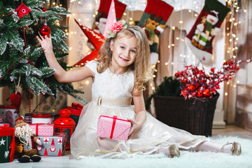 Pretty little blonde girl smiling with a flower hair clip and beige dress with present decorates a Christmas tree The concept of Christmas/