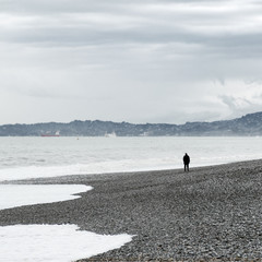 Lonely man in black clothes stands on the seashore in a cloudy day.