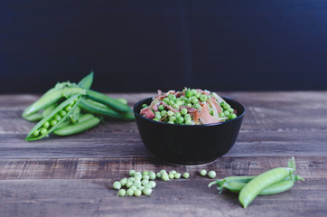 Bowl with peas and ham on wooden background.